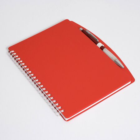 Red notebook with pen isolated on white Stock Photo