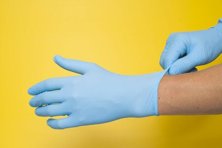Doctor putting on protective blue gloves isolated on yellow background