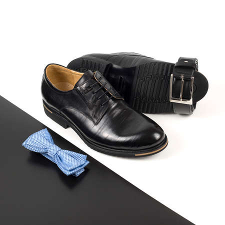 The black man's shoes and accessories isolated on white and black background.