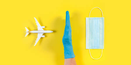Plane model and face medical mask on a yellow background. Doctor hand with glove