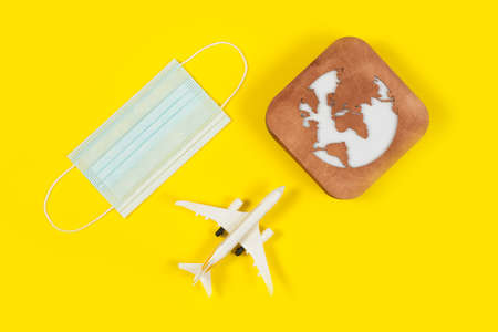 Plane model, face mask and earth model on a yellow background. Flight impact of coronavirus (COVID-19) concept.