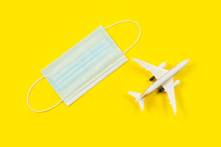Plane model and face mask on a yellow background. Flight impact of coronavirus (COVID-19) concept. 免版税图像