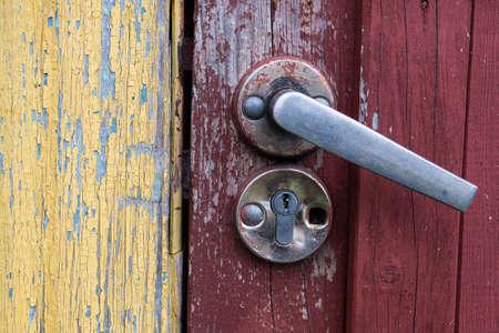 Old door handle on the red rusty door.