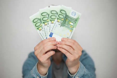 Businessman in blue shirt holds european euro money on white background, closeup. Money, earnings, crediting and finance. Фото со стока