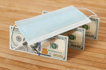 A medical blue mask lies on dollars with a face value of 100 dollars on a wooden background. 100 dollar bill and protection medical mask. Coronavirus. Financial assistance for medicine. Фото со стока