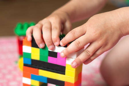 Small hands of the child collects the bright plastic colored Designer. Educational toys and Early learning
