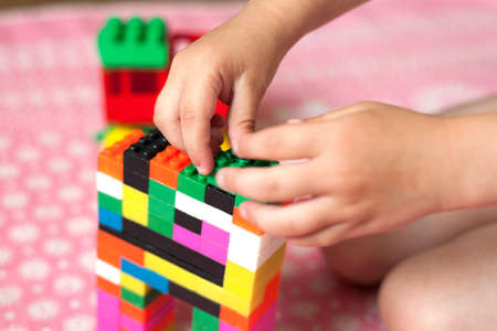 Small hands of the child collects the bright plastic colored Designer. Educational toys and Early learning Stok Fotoğraf - 159529248