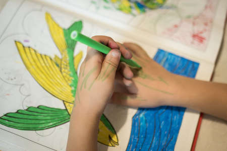 a child draws a pencil on a whitelist on a white table