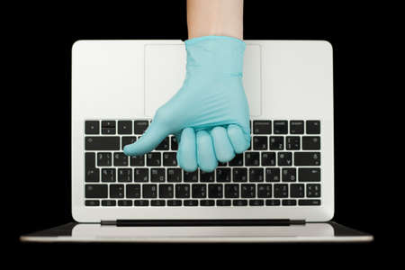 Hand in blue glove showing thumbs up. Portable laptop. Coronavirus protection. Stok Fotoğraf - 160661013