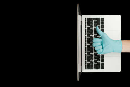 Hand in blue glove showing thumbs up. Portable laptop. Coronavirus protection.