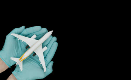 Hand in glove holding model airplanes on black background. Concept traveling. Copy space