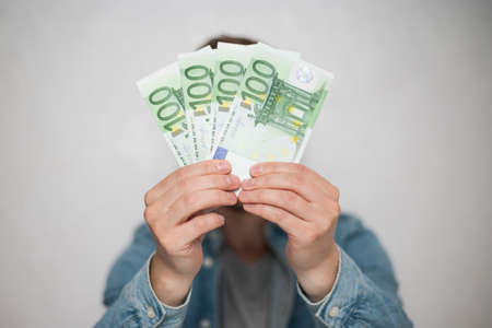 Businessman in blue shirt holds european euro money on white background, closeup. Money, earnings, crediting and finance. Stok Fotoğraf