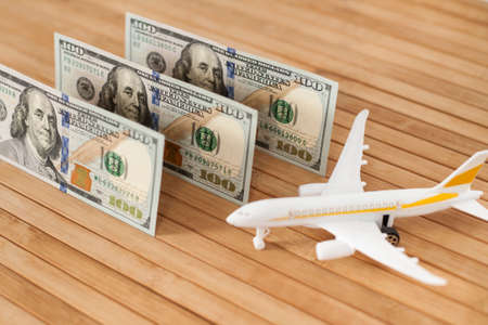 Plane model, face mask and and US dollars money on a wooden background with copy space. resumption of flights. opening of international flights after concept of coronavirus (COVID-19).