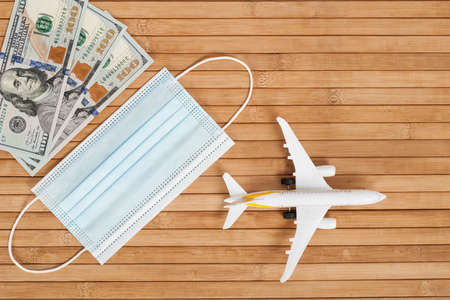 Plane model, face mask and money on a wooden background with copy space. resumption of flights. opening of international flights after concept of coronavirus (COVID-19). Stok Fotoğraf - 160215147