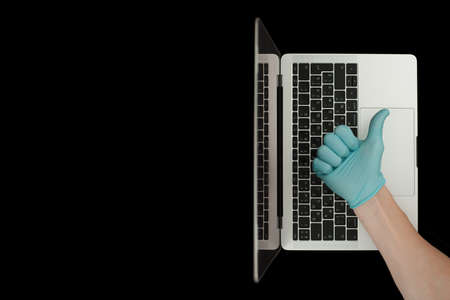Hand in blue glove showing thumbs up. Portable laptop. Coronavirus protection. Stok Fotoğraf - 161033999