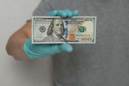 Hands in blue latex gloves hold dollars banknotes on white background. Money, earnings, crediting and finance.