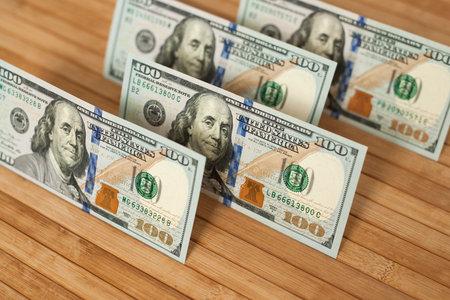 100 Dollars bill and portrait Benjamin Franklin on USA money banknote. Hundred dollar bills on wooden background.