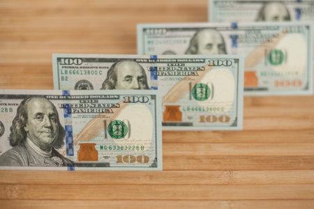 100 Dollars bill and portrait Benjamin Franklin on USA money banknote. Hundred dollar bills on wooden background. Stok Fotoğraf - 161034032