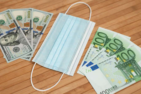 Money dollars, euro banknotes bill with face mask. Crisis and finance concept. COVID-19 coronavirus, pandemic. Mouth mask with euro and US dollar money on a wooden background.
