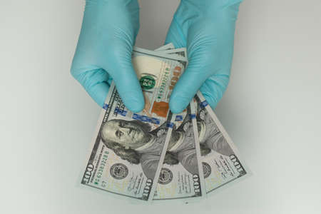 Hands in blue latex gloves hold dollars banknotes on white background. Money, earnings, crediting and finance. Stok Fotoğraf - 161034043