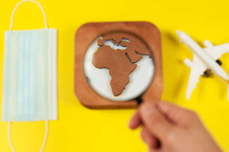 Plane model, face mask, loupe in hand and earth model on a yellow background. Flight impact of coronavirus (COVID-19) concept. Africa