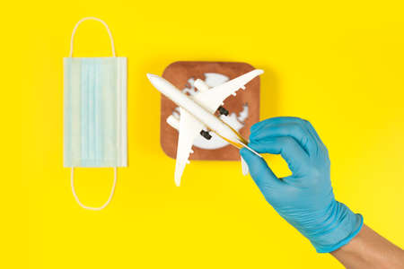 Plane model in hand, face mask and earth model on a yellow background. Hands in gloves. Flight impact of coronavirus (COVID-19) concept. Africa Stok Fotoğraf - 161089822