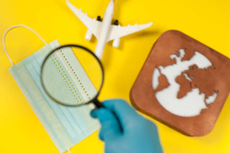 Plane model, face mask, loupe in hand and earth model on a yellow background. Hands in gloves. Flight impact of coronavirus (COVID-19) concept. Stok Fotoğraf - 161089825