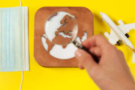 Plane model, face mask, loupe in hand and earth model on a yellow background. Flight impact of coronavirus (COVID-19) concept. Europpe