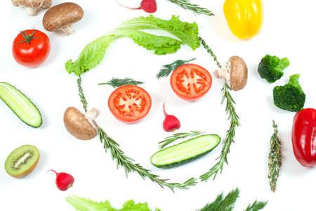Funny face from different vegetables tomatoes, cucumber, radish, dill and rosemary isolated on white background. Healthy eating and vegan food concept. Kitchen