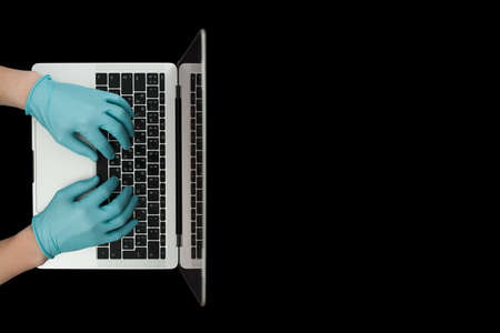 Hands in blue protective gloves typing on laptop keyboard. Top view. Stok Fotoğraf - 162051778