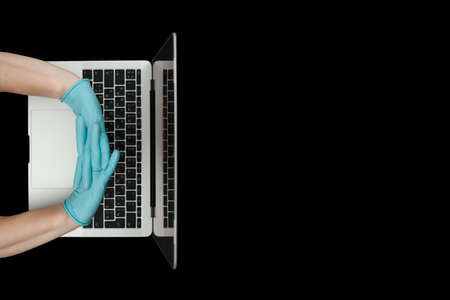 Hands in blue protective gloves typing on laptop keyboard. Top view.