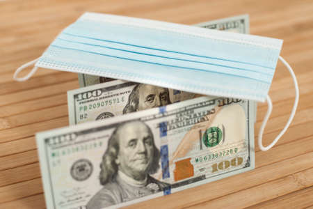 A medical blue mask lies on dollars with a face value of 100 dollars on a wooden background. 100 dollar bill and protection medical mask. Coronavirus. Financial assistance for medicine. Stok Fotoğraf
