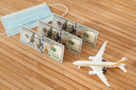 Plane model, face mask and and US dollars money on a wooden background with copy space. resumption of flights. opening of international flights after concept