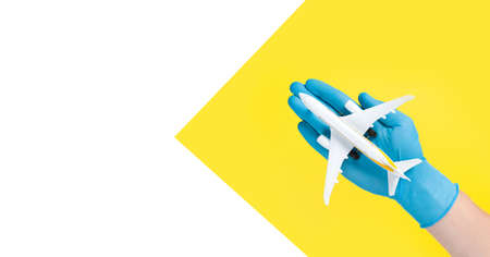 Hand in glove holding model airplanes on yellow background. Concept traveling. Copy space