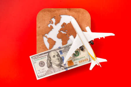 A globe, a toy plane and a 100 dollar bill on red background. Travel concept Stok Fotoğraf