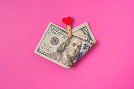 100 with a gift in the form clothespin of a red heart on pink background. Valentine's day concept background