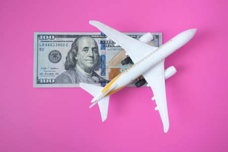 A globe, a toy plane and a 100 dollar bill on pink background. Travel concept Stok Fotoğraf