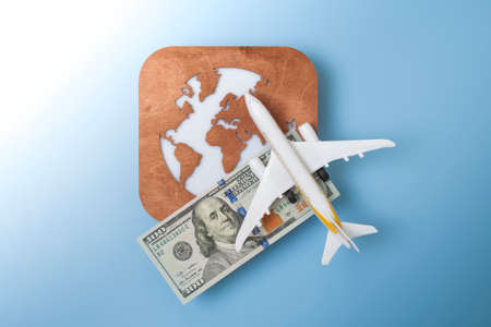 A globe, a toy plane and a 100 dollar bill on blue background. Travel concept
