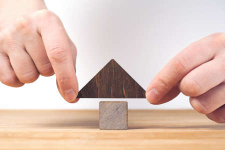 Real estate concept. Wooden house model on wooden table, white background