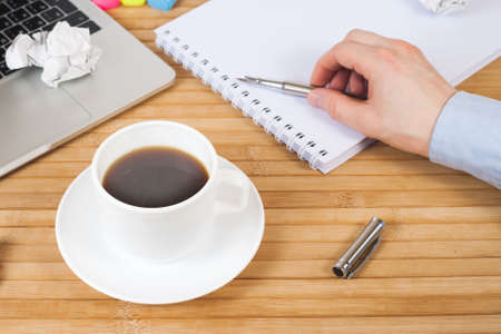 Male hand with pen on notebook, coffee cup, pen, markers, glasses and laptop on wooden table. Work space in office. Business, education, people and technology concept - close up of male hands with laptop and coffee cup Stok Fotoğraf