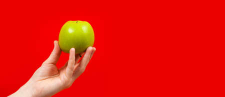 Hand holding tasty organic green delicious apple Isolated on red Background Stok Fotoğraf