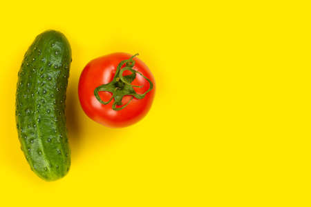 Beautiful fresh cucumber and tomato on yellow background. Ripe vegetables