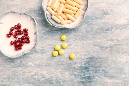 Vitamin C, Beta-Carotene tablets and Coenzyme Q10 capsules. Antioxidants. Concept for a healthy dietary supplementation. Bright wooden background. Top view. Copy space. Banco de Imagens