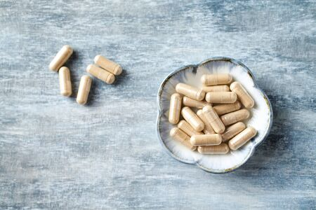Ashwagandha (Withania somnifera) capsules. Concept for a healthy dietary supplementation. Rustic wooden background. Top view. Copy space. Banco de Imagens