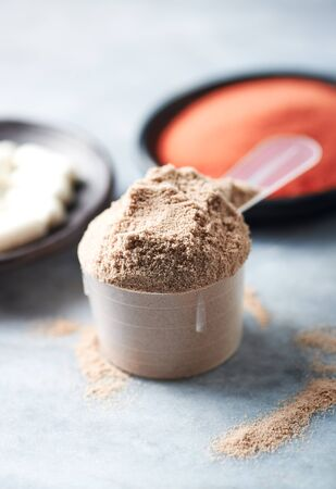 Scoop of Whey Protein, Beta-alanine capsules and Creatine Powder. Sport nutrition. Stone background. Copy space