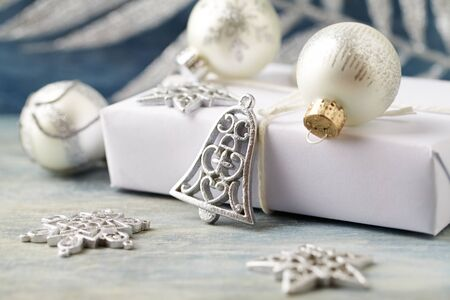 Christmas decoration and present. Christmas bell and silver baubles. Christmas time. Wooden background. Close up.