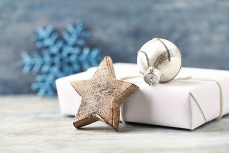 Wooden Christmas star, silver bauble and Christmas present. Christmas decoration. Christmas time. Wooden background.