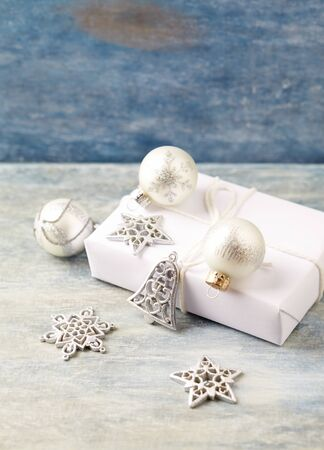 Christmas decoration and present. Christmas stars, bell and silver baubles. Christmas time. Wooden background.