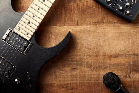 Body and fretboard of modern electric guitar, Multi effects Processor and microphone on rustic wooden background. Top view. Copy space. Stock Photo - 129683867