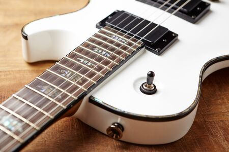 Body and fretboard of modern electric guitar on rustic wooden background. Stock Photo - 129683871